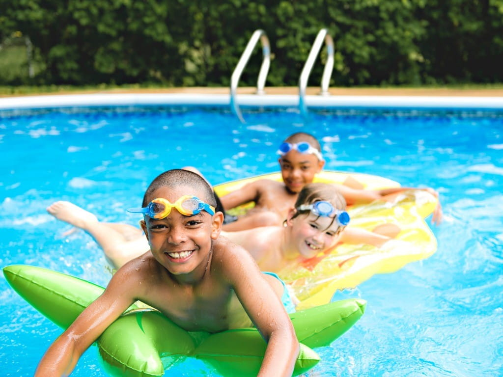 three kids swimming in chlorinated pool