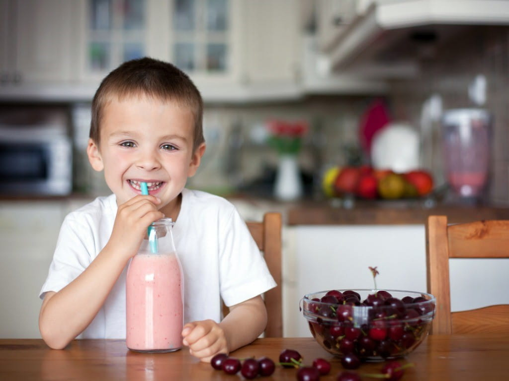 boy drinking cherry smoothie with bowl of cherries on table